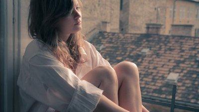 Garota com expressão triste sentada com janela ao lado