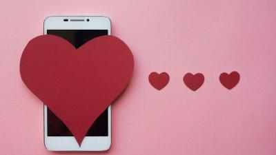 Celular com um coração grande recortado em cima e três outros corações pequenos ao lado.