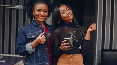 Meninas felizes segurando canecas em casa