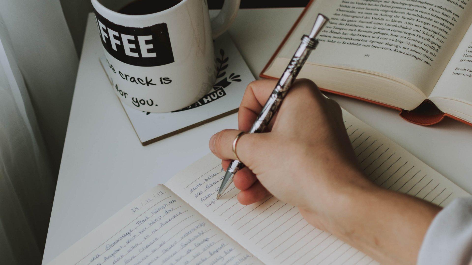 Mão escrevendo no caderno promessas de ano novo