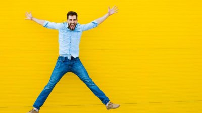 Homem saltando feliz em fundo amarelo