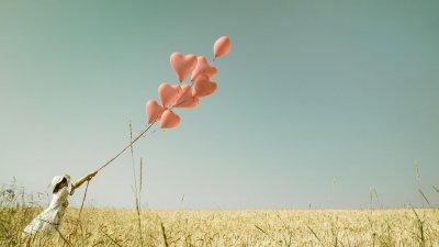 Menina segura balões em formato de coração