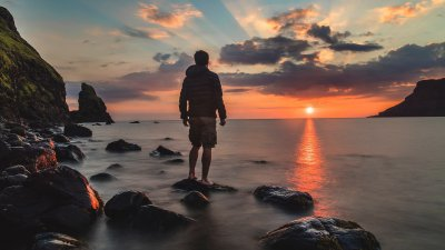 Homem em pé sobre uma rocha na praia, olhando para o mar, sob o pôr do sol.