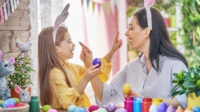 Mulher e menina, ambas usando tiaras de orelhas de coelho, pintando ovos, e as duas ameaçando a pintar o nariz da outra.