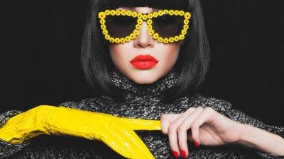Mulher com cabelo chanel e óculos de sol tirando luva amarela