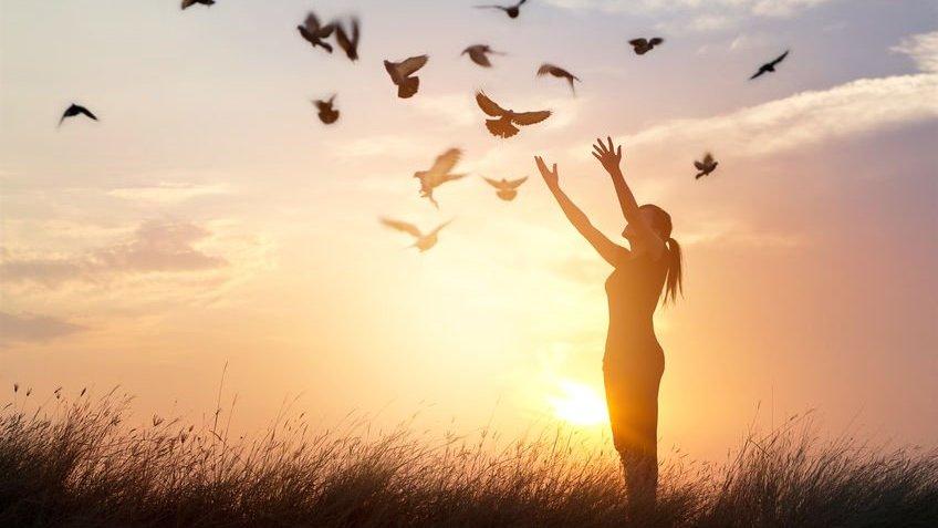 Mulher com os braços levantados enquanto vários pássaros voam