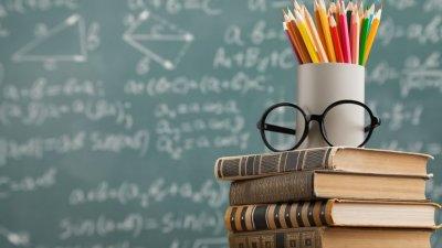Mesa com livros, óculos e copo com lápis de cor