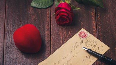 Um estojo de anel em veludo vermelho e formato de coração, uma carta e uma caneta sobre uma mesa de madeira.