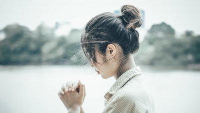 Mulher de cabelos presos cabisbaixa, com as mãos unidas em frente ao rosto.