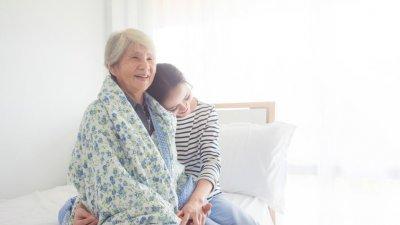 Mulher abraçando uma senhora idosa, que sorri