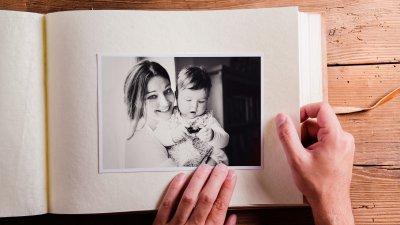 Mãos sobre um álbum de fotos antigas, com uma foto de uma mãe segurando seu filho no colo