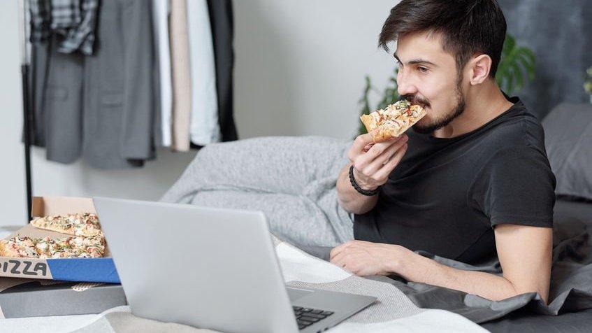 Homem deitado em cama, comendo pizza, enquanto assiste algo em notebook.