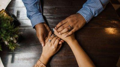 Mãos dadas sobre uma mesa de madeira.