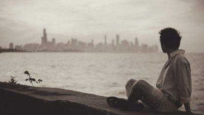 Homem olhando para o mar e a cidade que está longe