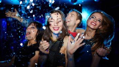 Amigos sorrindo e celebrando com artigos de festa.