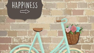 Placa escrito happiness em cima de uma bicicleta.