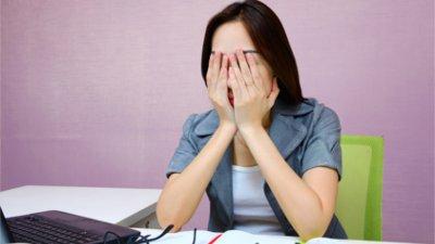 Mulher sentada em uma mesa de escritório com as mãos sobre o rosto.