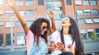 Duas jovens rindo, ouvindo música dividindo fone de ouvido. Uma segura o celular, e a outra tem os braços erguidos.