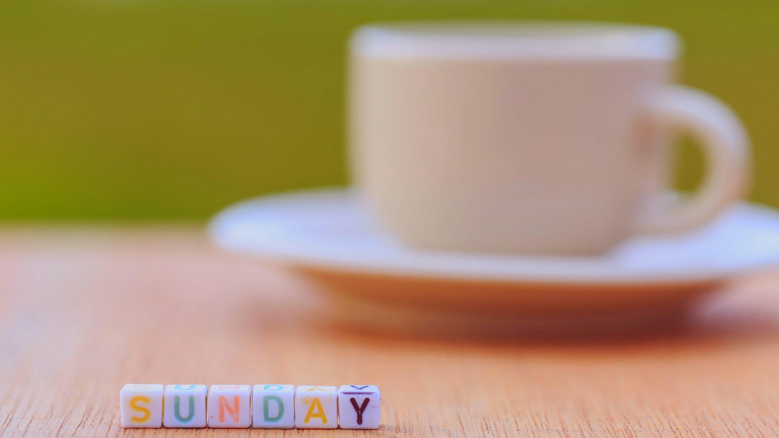Mesa com xícara branca e miçangas coloridas formando a palavra