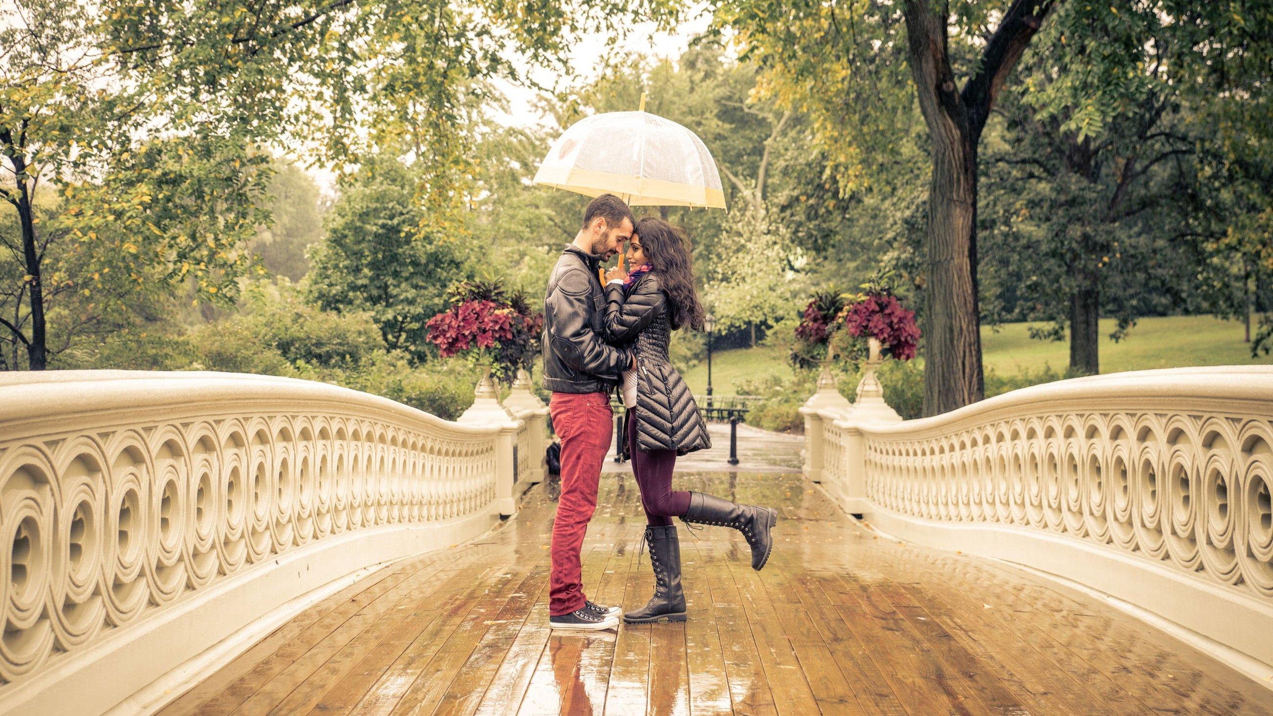 Casal abraçado sob um guarda-chuva