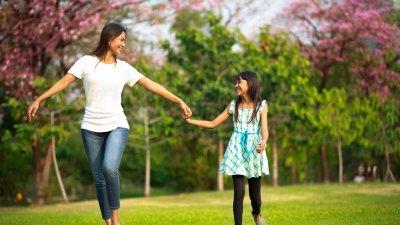 Tia e sua sobrinha passeando em um parque durante o dia.