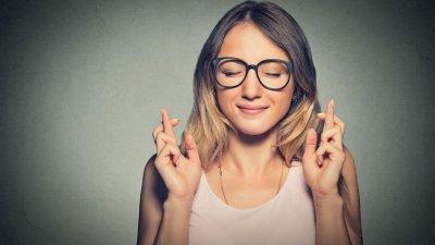 Mulher fazendo figas com os dedos e olhos fechados em fundo cinza