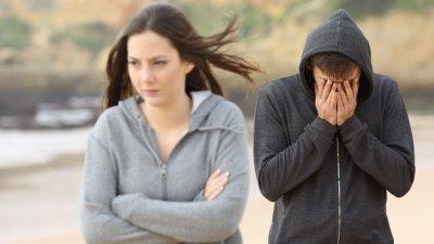 Foto de mulher indo embora e homem com as mãos no rosto