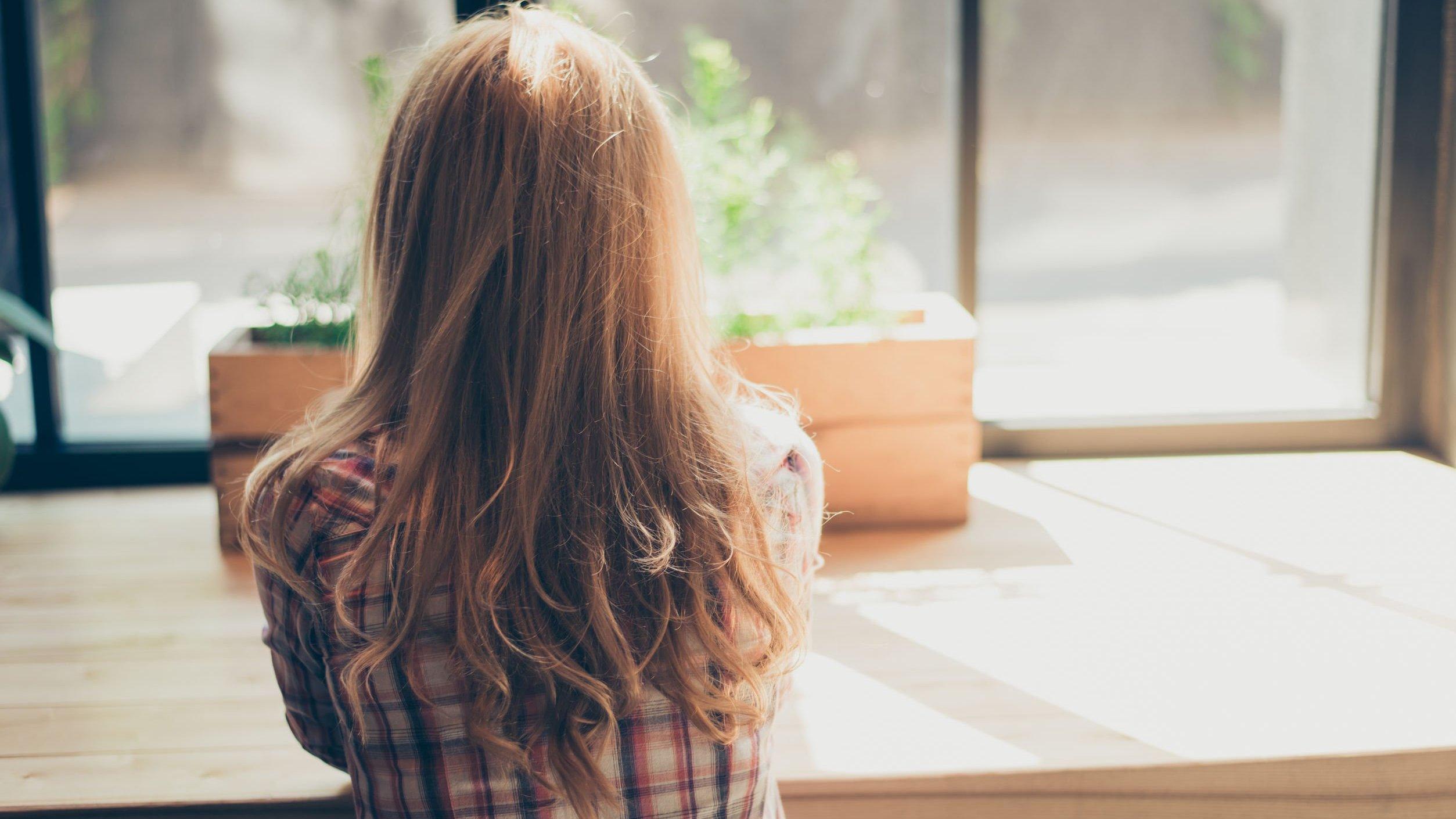 Mulher olhando para a janela de cabelos soltos usando blusa xadrez