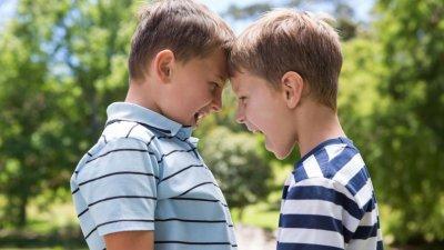 Dois primos crianças encostando as testas enquanto riem