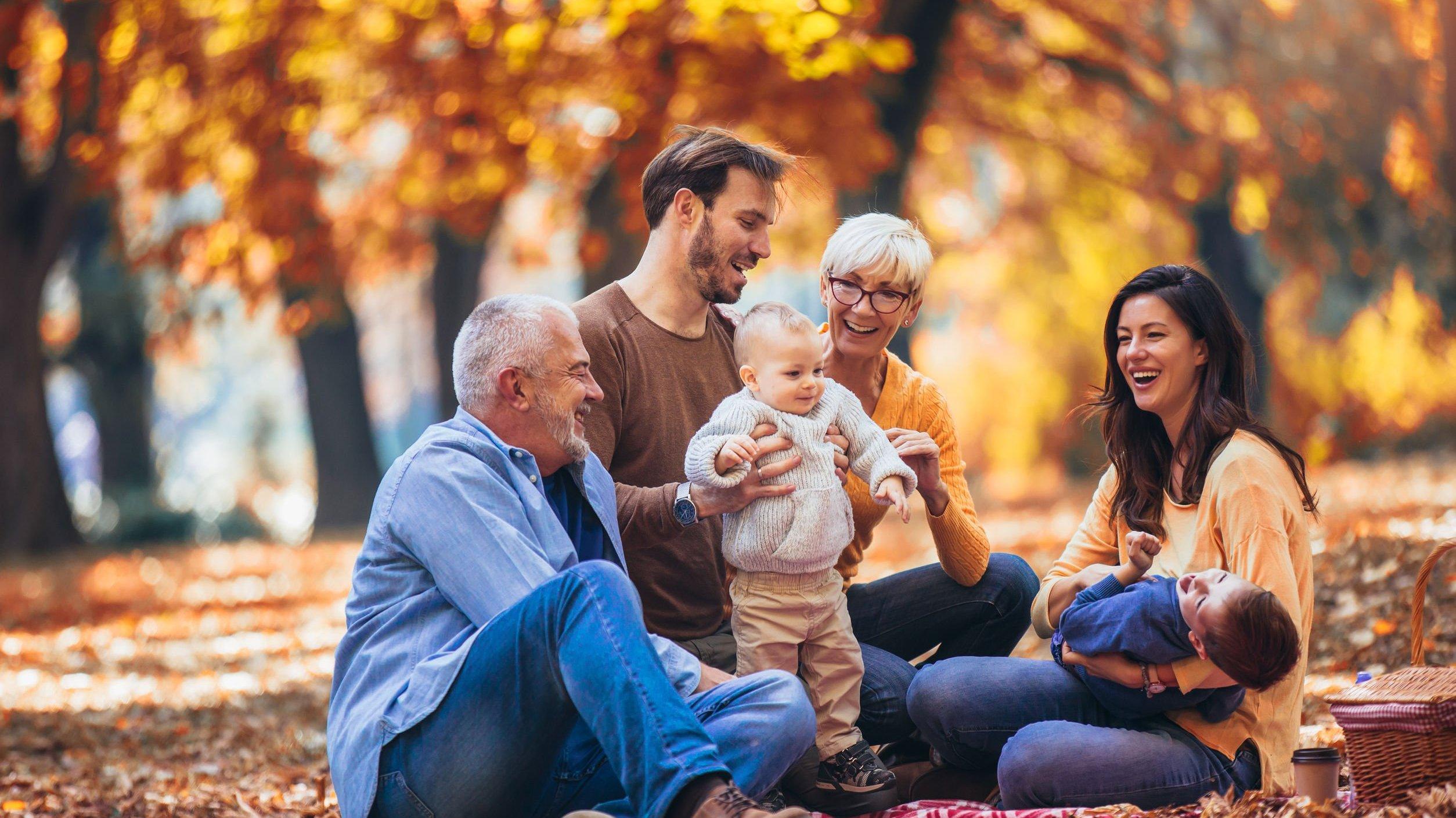 Família composta de por idosos, adultos e crianças em um cenário outonal