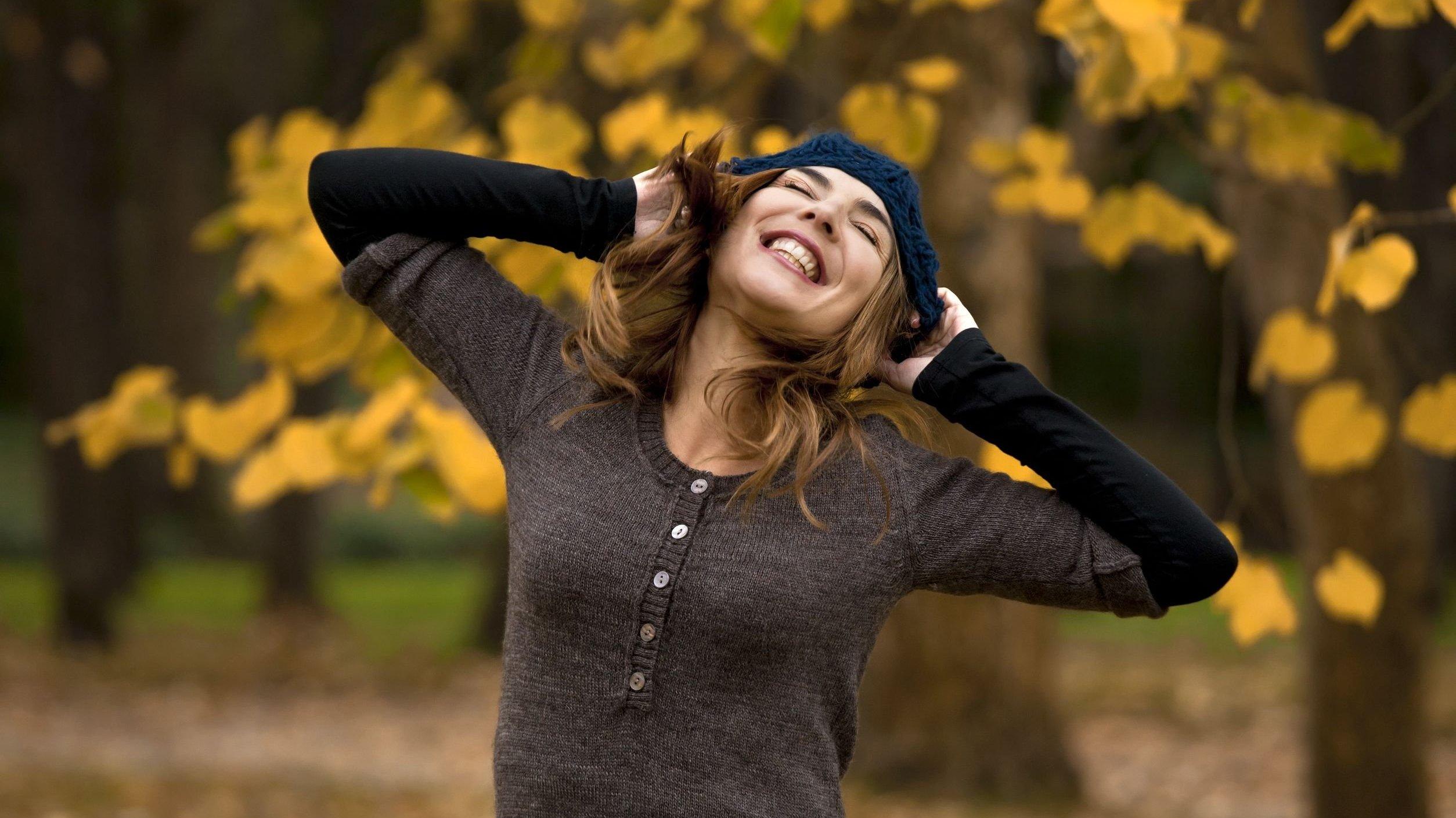 Mulher sorrindo em um jardim de olhos fechados