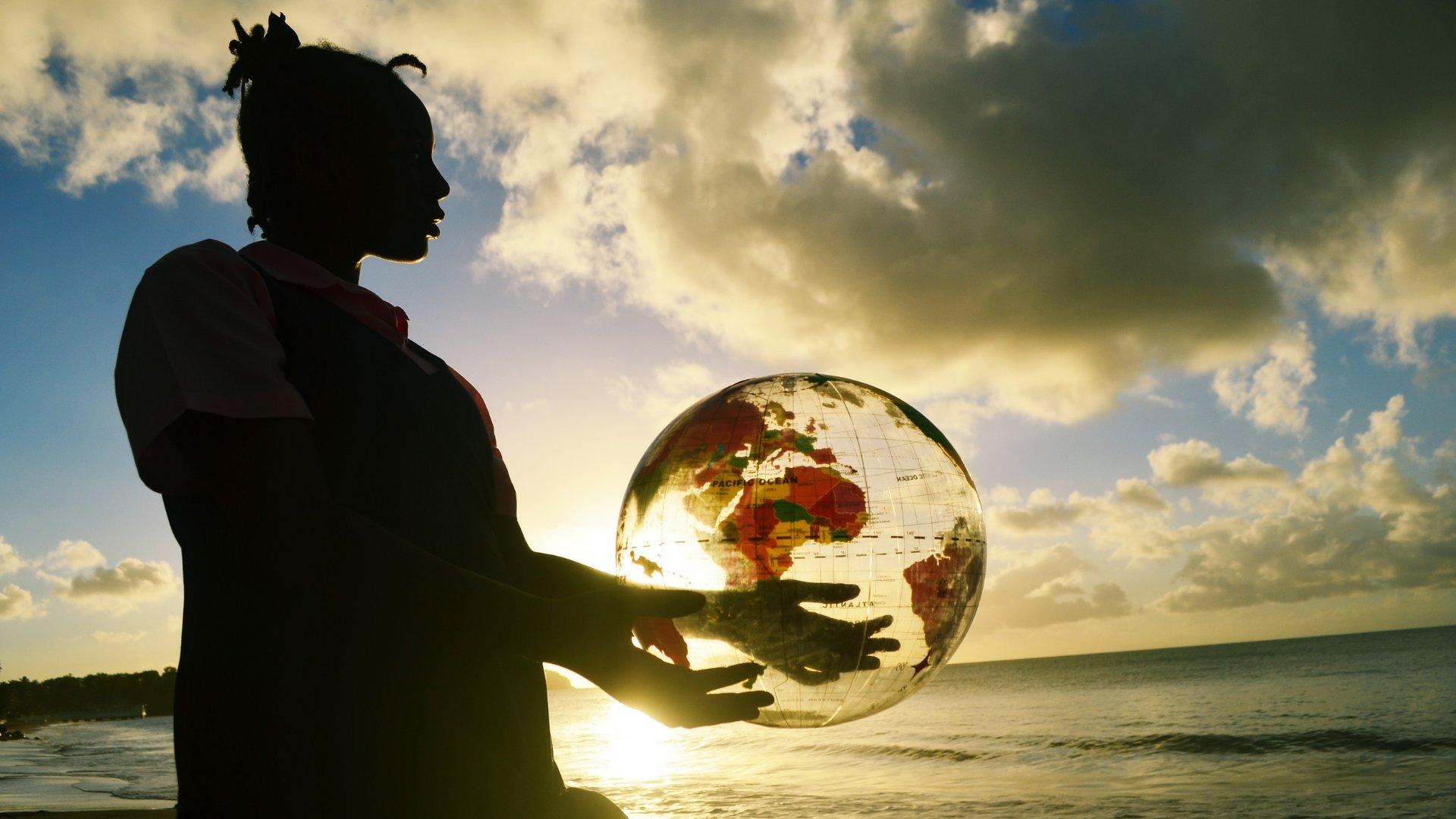 Silhueta de mulher segurando o globo terrestre enquanto admira o pôr do sol