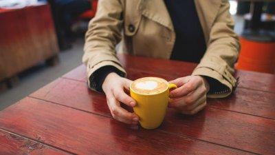 Pessoa vestindo casaco, sentada, apoiando os braços em uma mesa enquanto segura uma caneca com café com leite, e espuma em formato de coração.