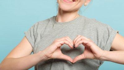 Mulher sorrindo com as mãos sobre o coração.