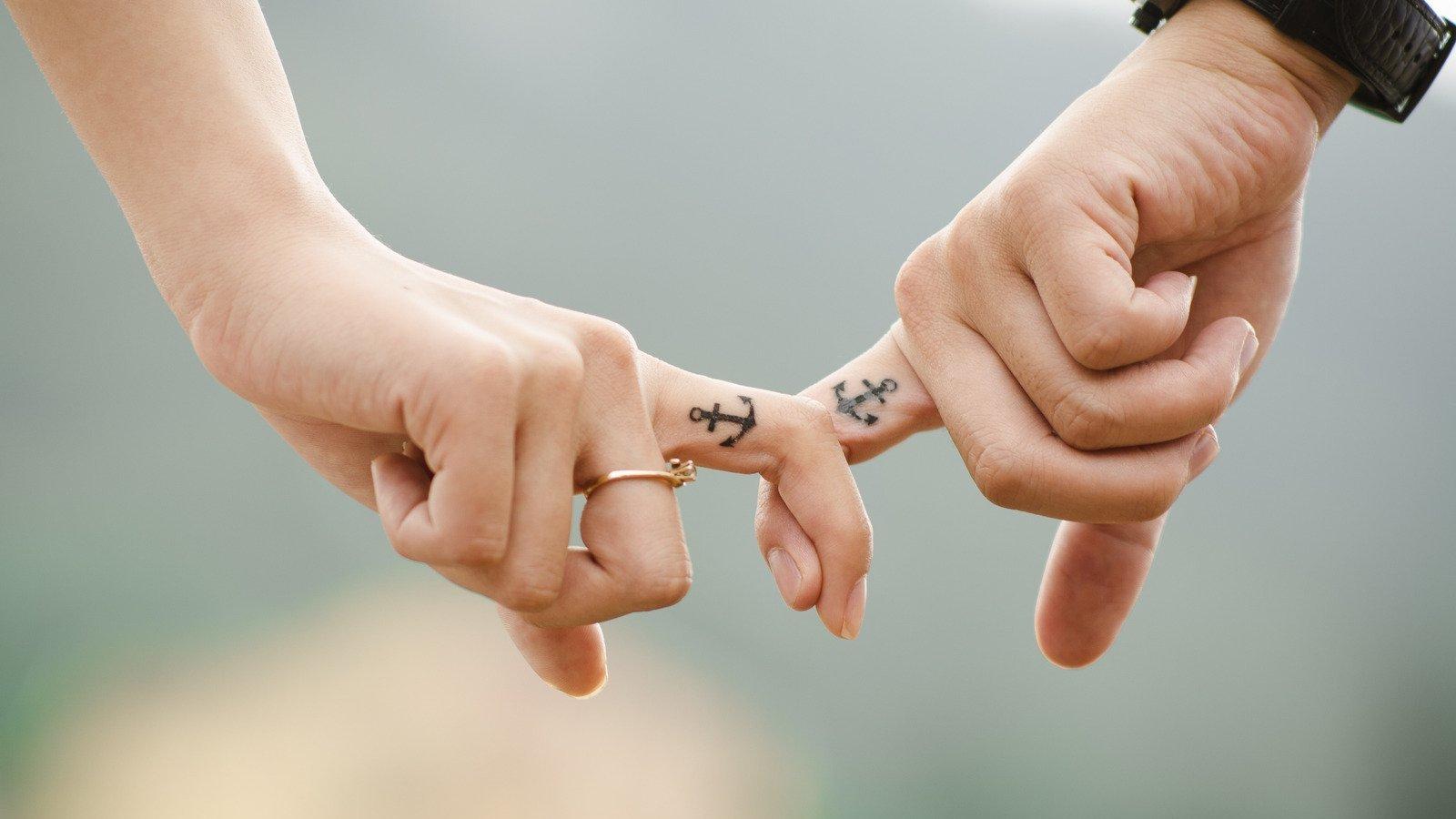 Indicadores feminino e masculino entrelaçados, com tatuagem de âncora.