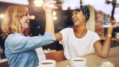 Duas mulheres em uma cafeteria batendo as mãos em um
