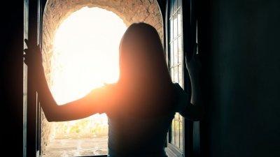 Mulher abrindo a janela e vendo o Sol