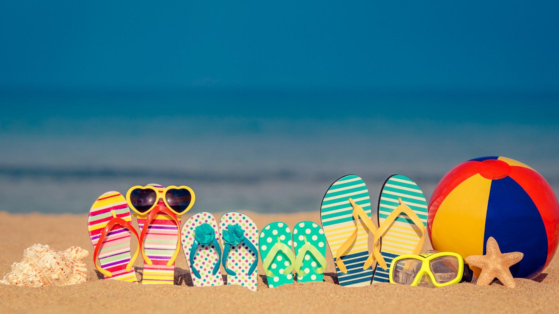 Chinelos de uma família enterrados na areia da paria junto de óculos de sol e bola de praia