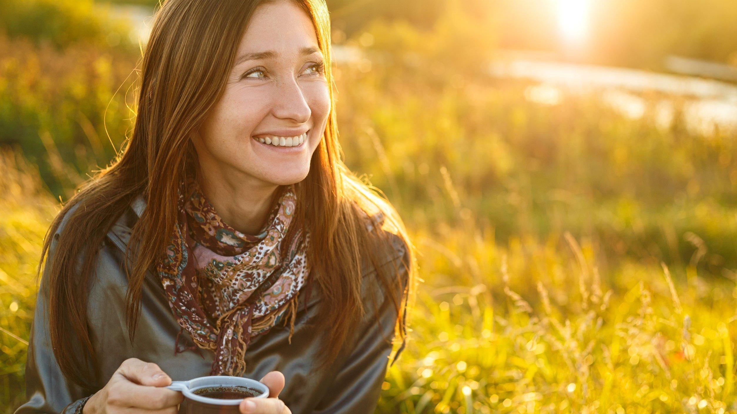 Mulher sentada em um gramado segurando uma xícara de café e sorrindo