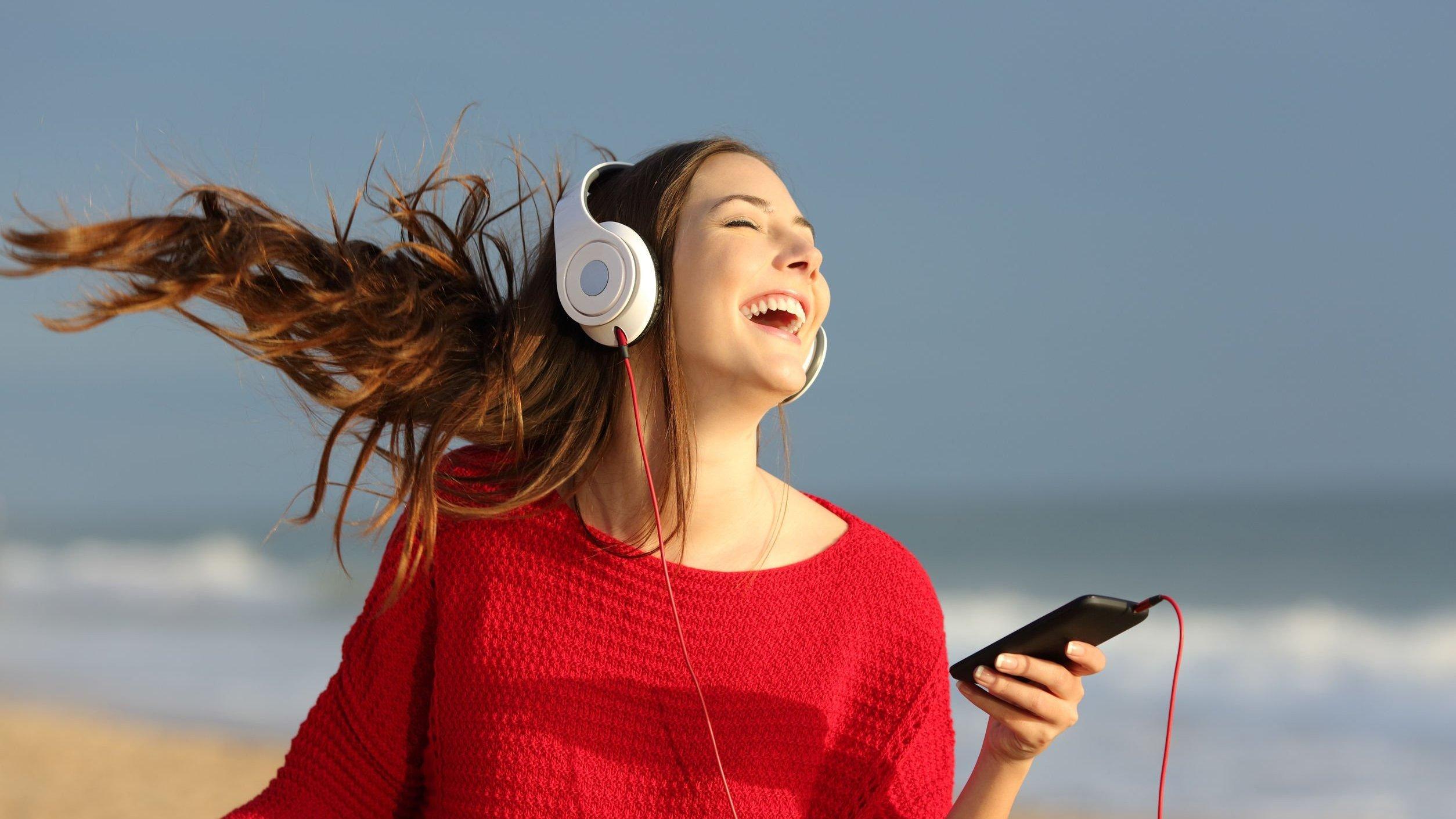 Mulher sorridente ouvindo música com fones de ouvido