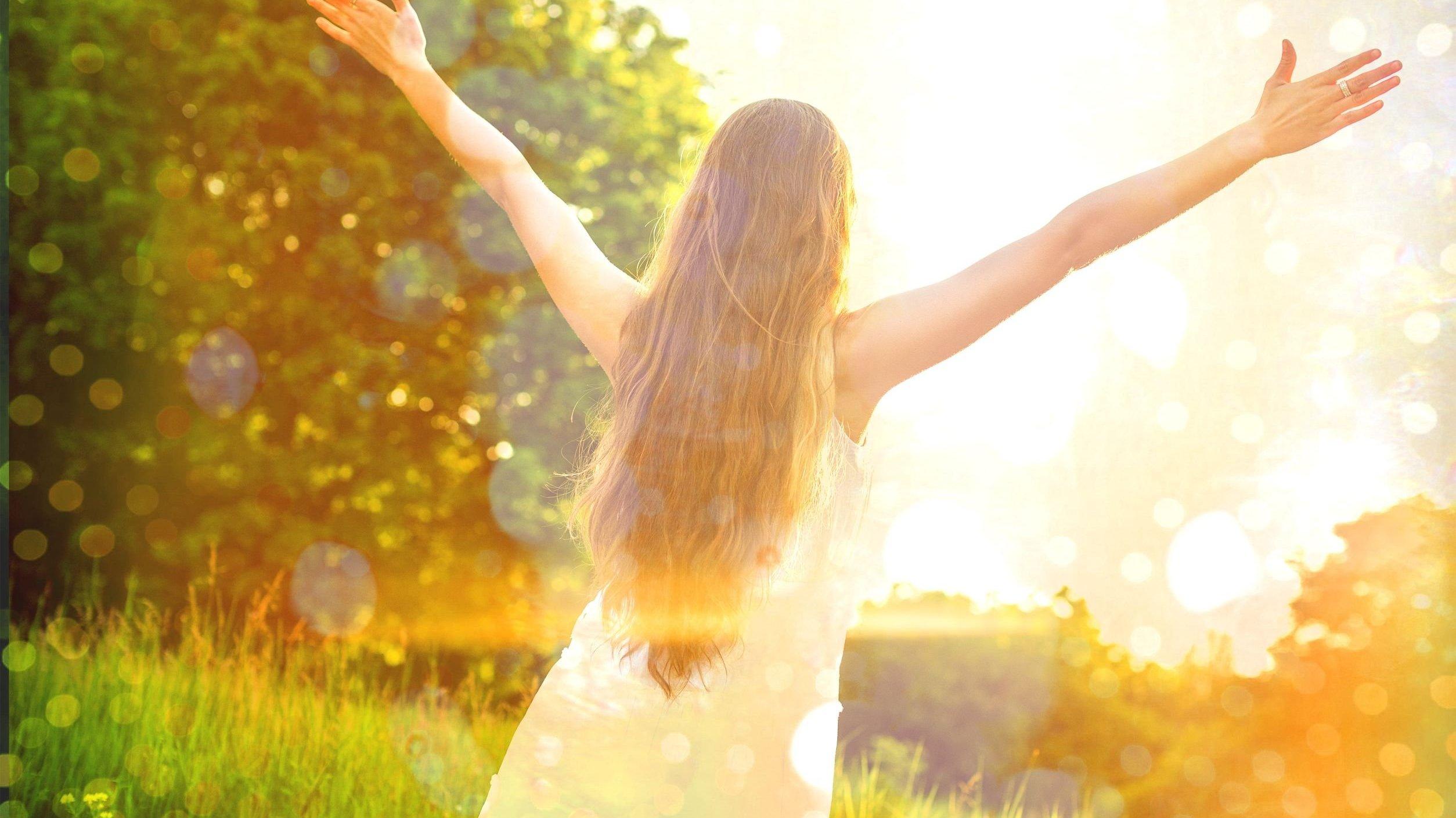 Mulher com os braços erguidos em ambiente externo.