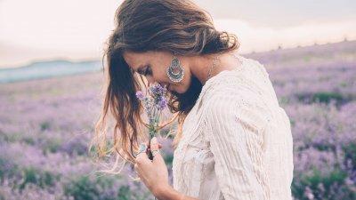 Mulher em um campo de flores, segurando uma flor e a cheirando