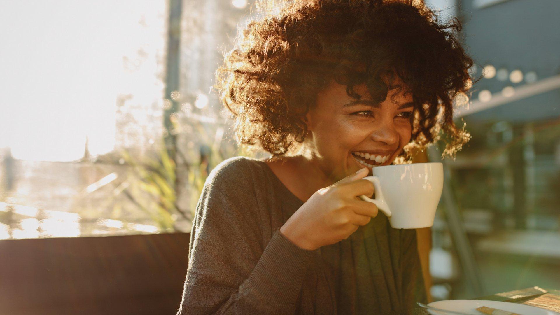 Mulher sentada em um café sorrindo enquanto toma uma xícara de café