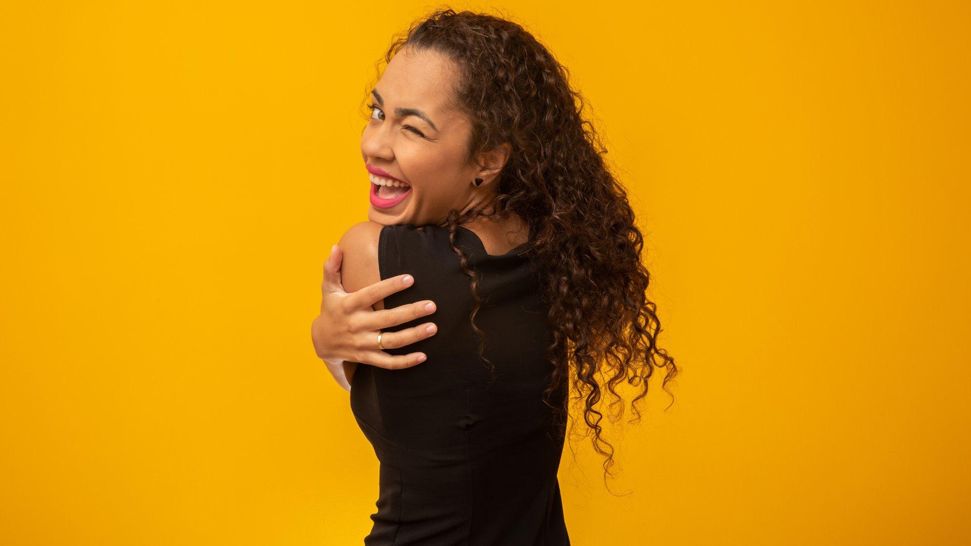 Mulher negra se abraçando enquanto sorri e pisca em um fundo amarelo
