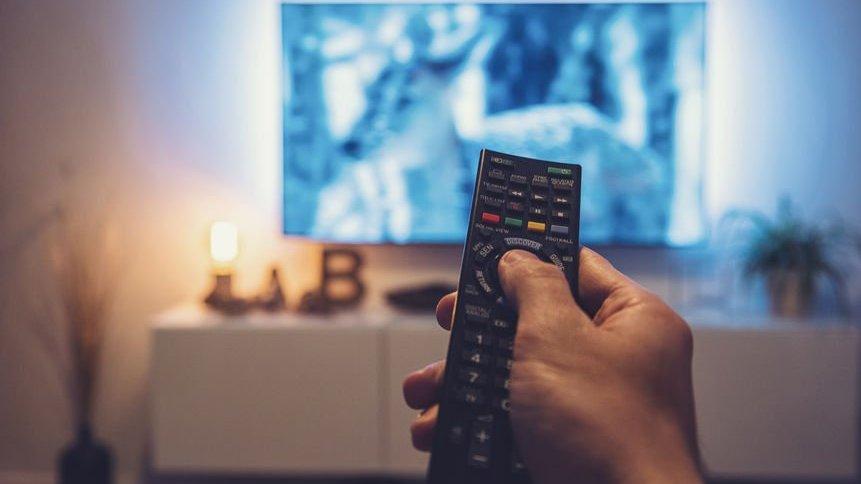 Pessoa segurando controle remoto em frente a uma televisão.