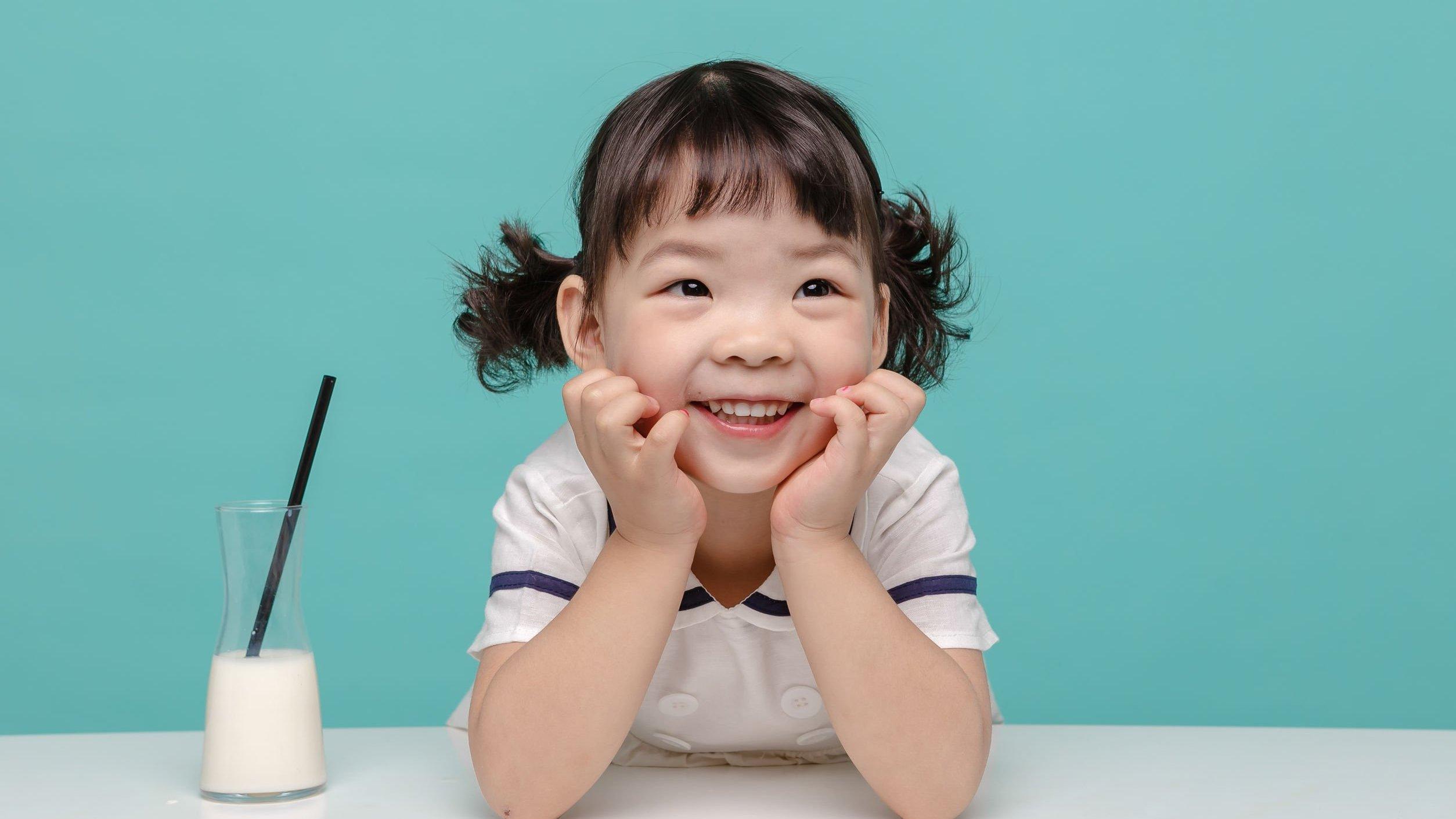 Criança sorrindo com as mãos sobre o rosto ao lado de um copo de leite