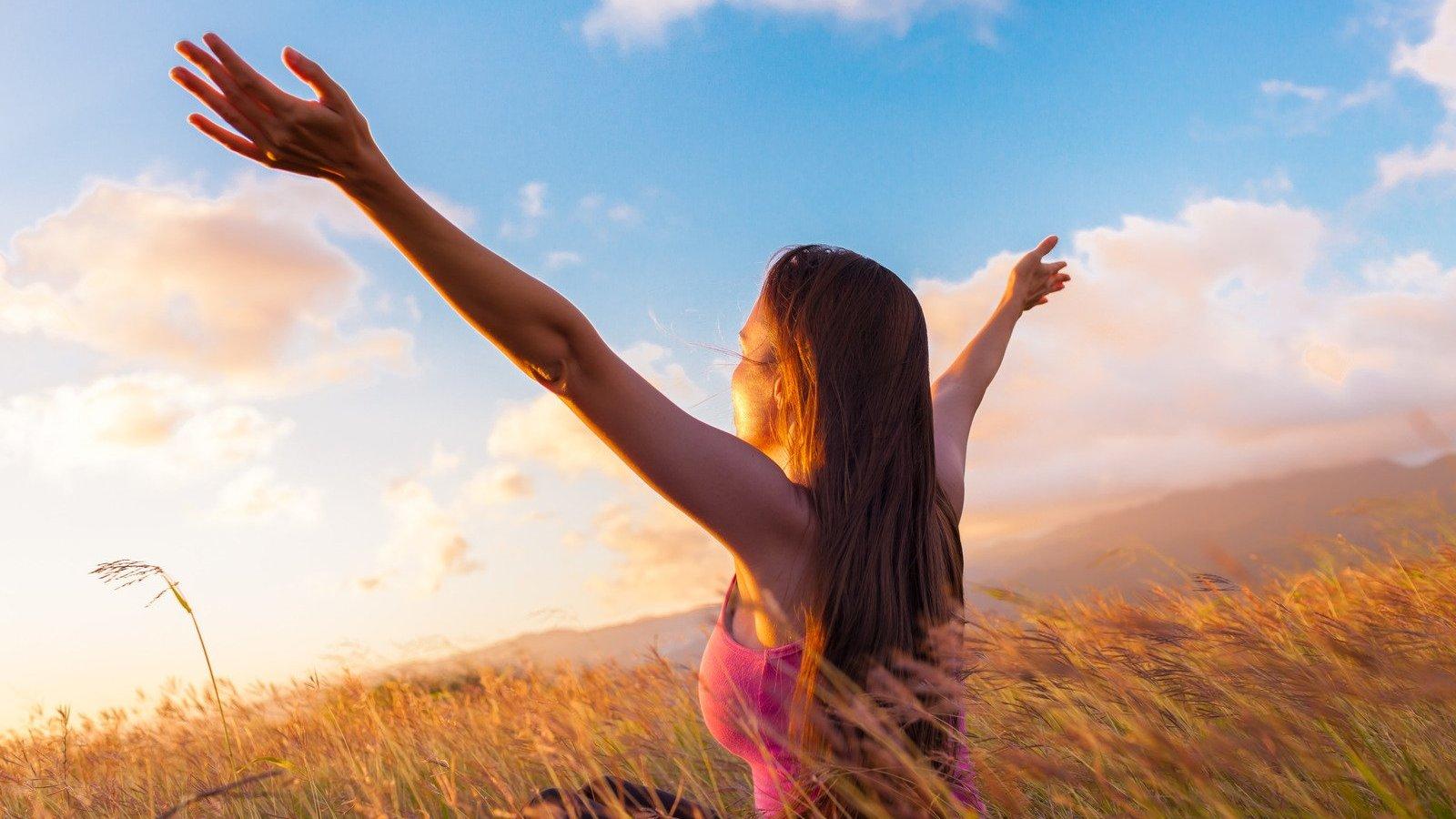 Mulher branca de costas num campo, com os braços abertos, com raios de sol no rosto.