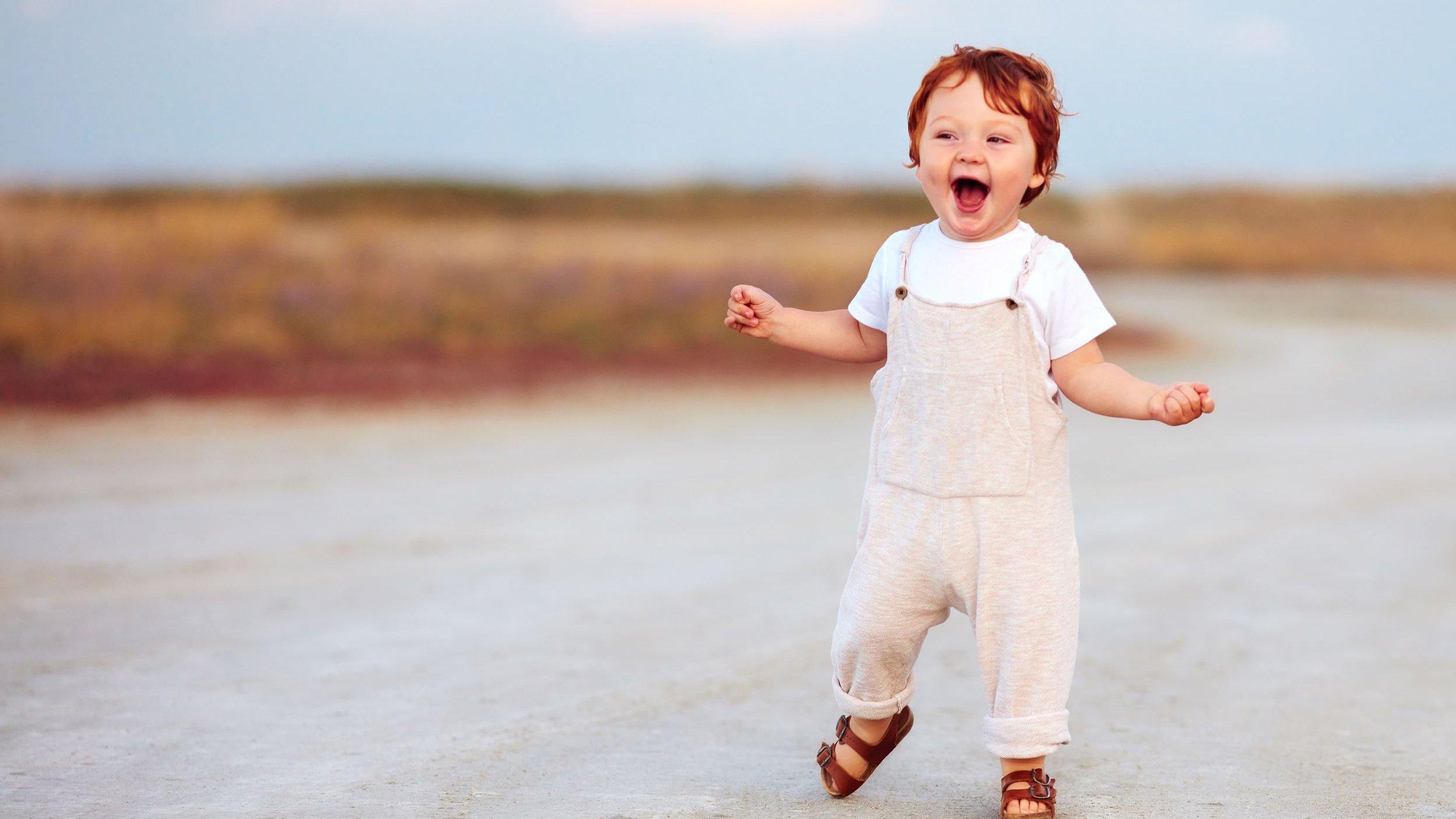 Bebê na rua usando macacão e sorrindo com os braços abertos