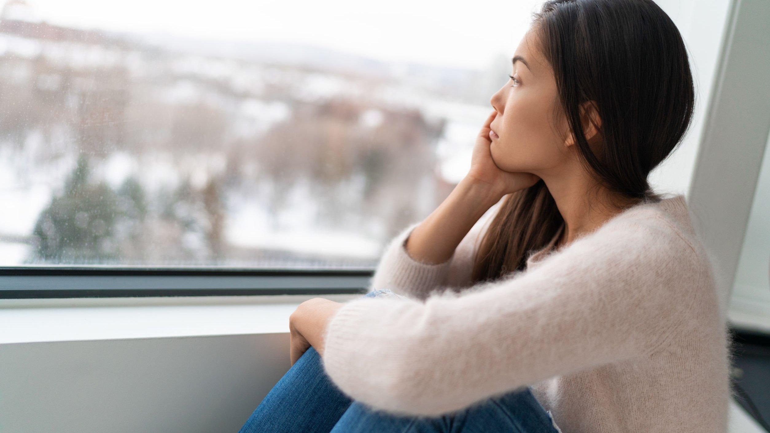 Mulher olhando para a janela triste