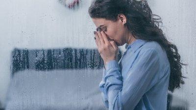 Mulher branca com mãos no rosto chorando